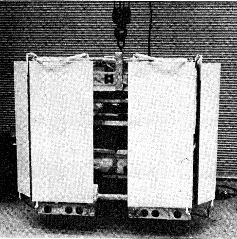 Frontal view of the gondola showing the overall cubic structure. The front radiator panels are prominant, with the viewings lot for the telescope. The pressure domes have been left off the package, permitting viewing of the interior of the experiment