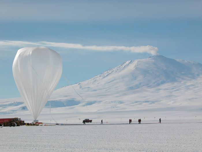 The balloon already inflated waiting for launch. In the background a smoke trail from Mt. Erebuz