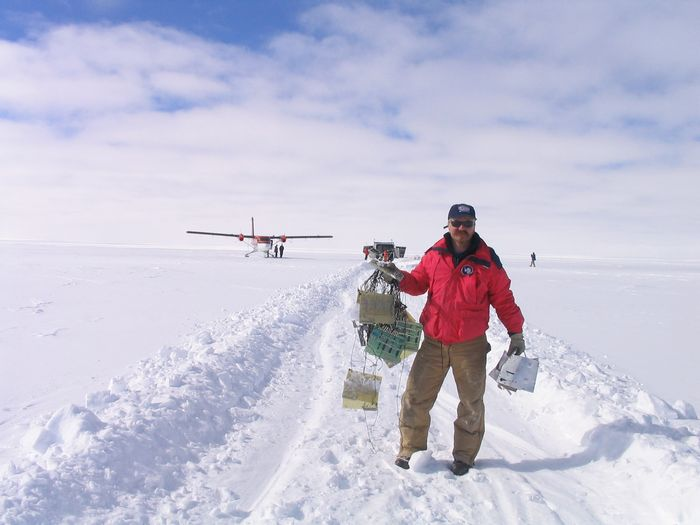 The trail left by TRACER on the plateau after being dragged by the undetached parachute. The technician holds in her hands some components of the instrument left in the ground due to dragging.
