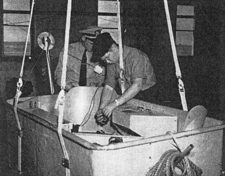 Navy technicians installing miniature transmitter in the open gondola which will transmit physiological data during balloon flight