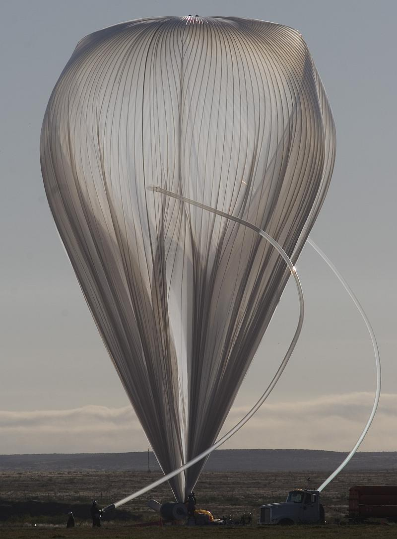 View of the balloon while being inflated. The inflation tubes are curved by effect of the strong wind (Photo by Carlye Calvin, UCAR)